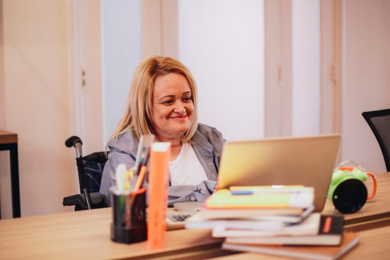 projeto Adobe MulheresInvisiveis - foto de uma mulher cadeirante sorrindo e trabalhando no computador, retirada do acervo do projeto